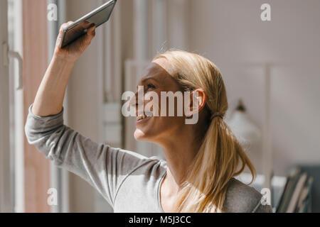 Femme souriante avec ses yeux de blindage tablet Banque D'Images