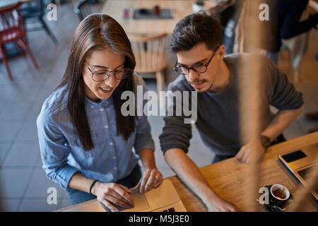 Jeune femme et l'homme dans un café avec un ordinateur portable Banque D'Images