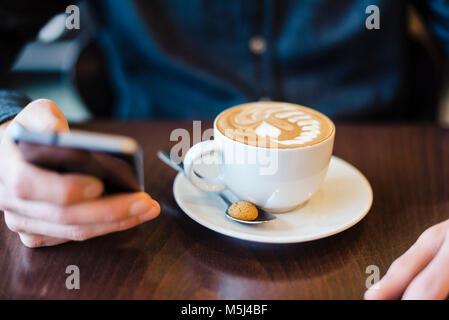L'homme à l'aide de téléphone cellulaire dans un coffee shop, close-up Banque D'Images