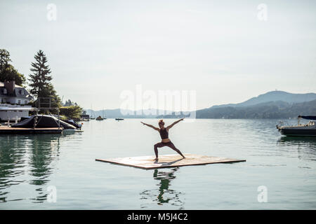Woman practicing yoga on raft dans un lac Banque D'Images