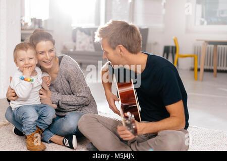 Famille heureuse assise sur le sol avec le père qui joue de la guitare Banque D'Images