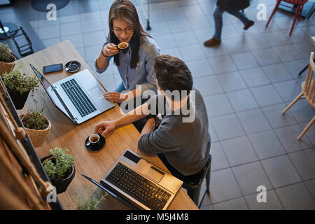 Jeune femme et l'homme dans un café avec des ordinateurs portables de parler et de boire l'expresso Banque D'Images