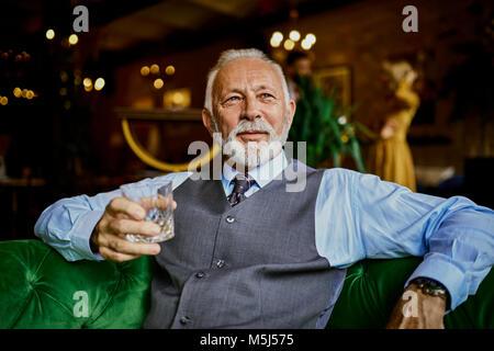 Portrait d'élégante senior man sitting on couch in a bar holding tumbler Banque D'Images