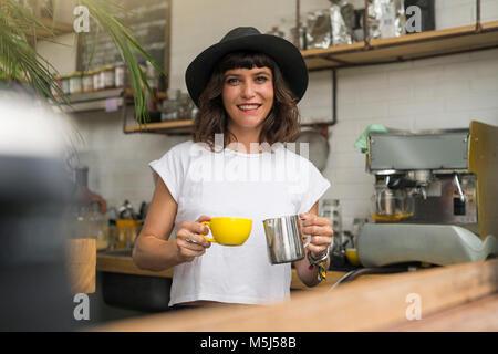 Portrait de femme au chapeau noir derrière le bar la préparation d'un café Banque D'Images