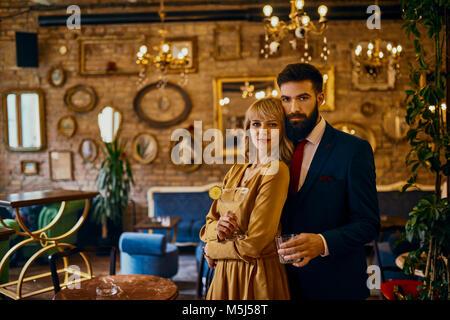 Portrait de couple élégant avec des boissons dans un bar Banque D'Images
