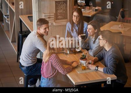 Groupe d'amis heureux assis ensemble dans un café avec un ordinateur portable et des boissons