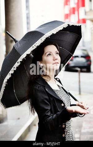 Portrait de jeune femme à la mode avec parapluie vintage noir Banque D'Images