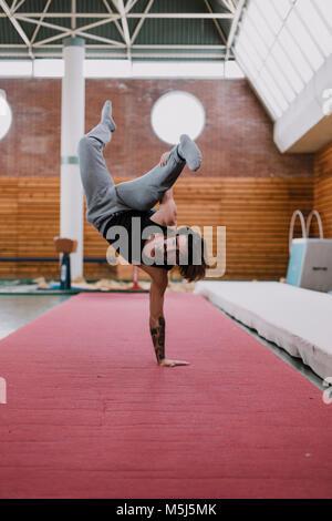 Jeune homme faisant l'exercice acrobatique in gym Banque D'Images