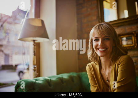 Portrait of smiling elegant woman sitting on a couch Banque D'Images