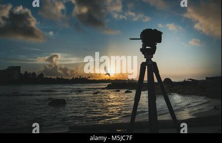 Comité permanent de l'appareil photo sur trépied au lever du soleil, mer des caraïbes, paysage Banque D'Images