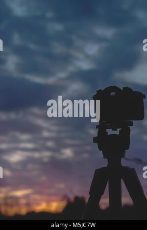 Comité permanent de l'appareil photo sur trépied au coucher du soleil, ciel, paysage, printemps, dans l'Oural Banque D'Images