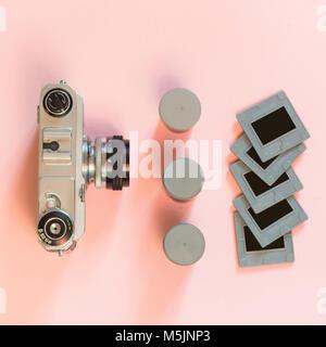 Ancienne rétro appareil photo avec trois fort du film et quelques diapositives sur fond rose. Concept. Banque D'Images