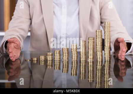 Close-up of Businesswoman mains protégeant les pièces empilées sur la table Banque D'Images