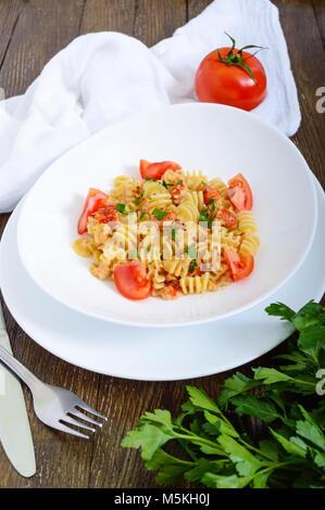 Salade de fruits de mer dans un bol blanc sur un fond de bois. Radiatori pâtes aux écrevisses, crevettes, tomates, Banque D'Images