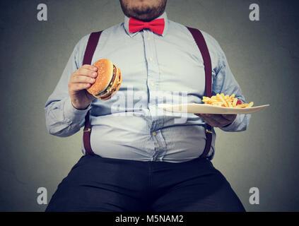 Petit coup de grand homme dans des vêtements formels assis et de consommer la plaque avec restauration rapide sur Banque D'Images