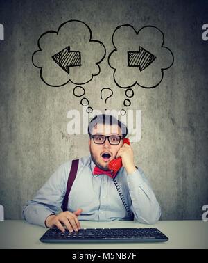 Businessman avec clavier parlant sur un téléphone dans l'incertitude quant à l'étape suivant Banque D'Images