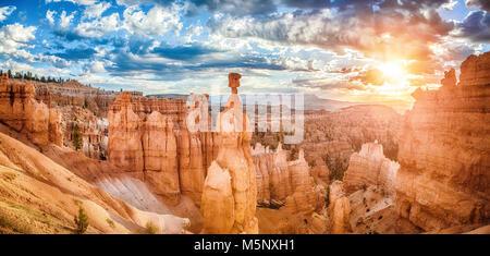 Des formations de grès étonnantes cheminées dans le Parc National de Bryce Canyon à golden lumière du matin au lever du soleil avec des nuages, de l'Utah, sud-ouest américain