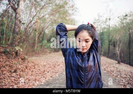 Asie femme athlétique de préchauffage et jeunes femmes athlètes de l'exercice et s'étend dans un parc avant Runner, Banque D'Images
