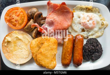 Le petit déjeuner anglais complet en œuf frit, bacon, haricots blancs, blanc muffin, boudin noir, tomates grillées, Banque D'Images