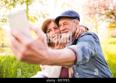 Couple avec le smartphone à l'extérieur au printemps la nature. Banque D'Images