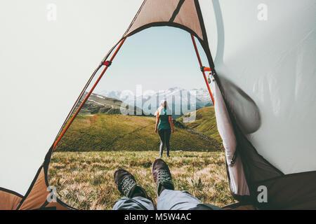 Camping voyage couple vue depuis l'entrée de la tente dans les montagnes à pied femme homme intérieur relaxant pieds Banque D'Images