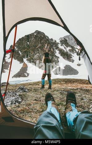 Vie Voyage couple camping vue depuis l'entrée de la tente dans les montagnes à pied femme homme intérieur relaxant Banque D'Images