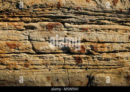 Arrière-plan de la pierre naturelle. Close-up un mur d'ardoise de montagne en couches roux. Banque D'Images