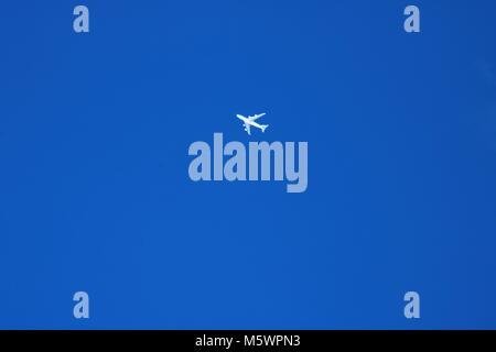 Avion blanc très haut dans un ciel d'hiver bleu Banque D'Images