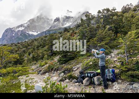 Trekker femme fait une pause pour boire de l'eau; au-delà de la Cordillère Paine; Parc National Torres del Paine, Banque D'Images