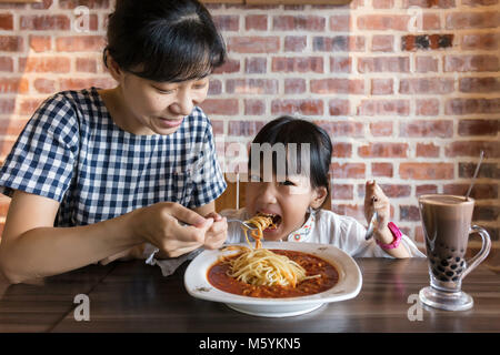 Chinois asiatique mother and daughter eating spaghetti bolognese dans le restaurant Banque D'Images