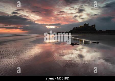 Lever de soleil sur plage de Bamburgh et château, Northumberland, Royaume-Uni Banque D'Images