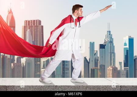 Jeune médecin de super-héros en cape rouge contre City Skyline Banque D'Images