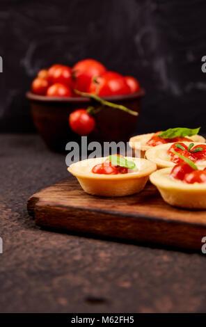 Mini tartelettes aux tomates cerises de fromage mozzarella sur planche de bois. Banque D'Images
