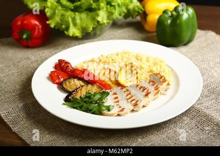 Avec des tranches de poulet grillé, avec légumes, couscous, sur une assiette blanche, décorée de persil. Dans l'arrière Banque D'Images
