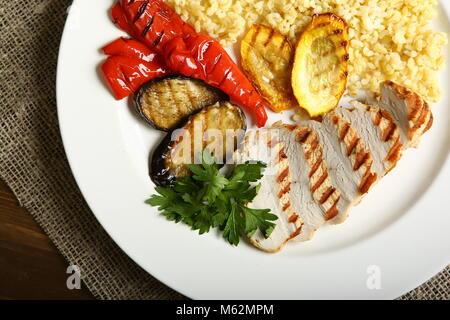 Avec des tranches de poulet grillé, avec légumes, couscous, sur une assiette blanche, décorée de persil. Faible Banque D'Images