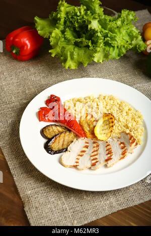 Avec des tranches de poulet grillé, avec légumes, couscous, sur une assiette blanche. Dans l'arrière-plan, feuilles Banque D'Images