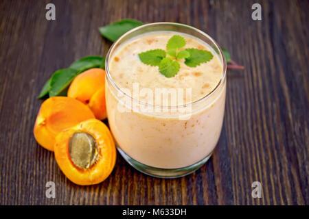 Un verre de lait aromatisé à l'Abricot, la menthe sur une planche en bois historique Banque D'Images