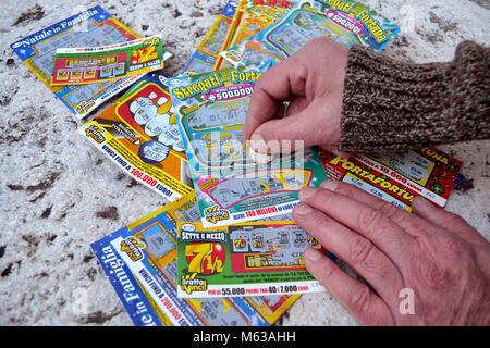 Un homme se gratter une carte à gratter loterie