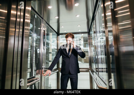 Business man walking while talking on mobile phone sur le chemin du travail Banque D'Images