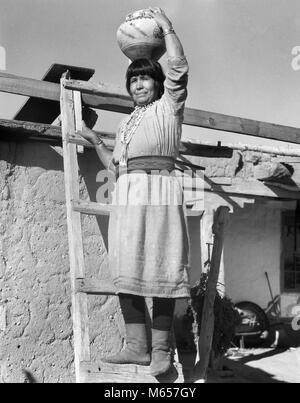 1930 Native American Indian WOMAN HOLDING sur l'échelle JAR POTERIE OLLA sur sa tête Cochiti Pueblo NOUVEAU MEXIQUE Banque D'Images