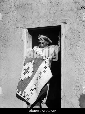 1930 SMILING Native American Indian MAN STANDING IN DOORWAY portant des costumes typiques de SAN ILDEFONSO PUEBLO Banque D'Images