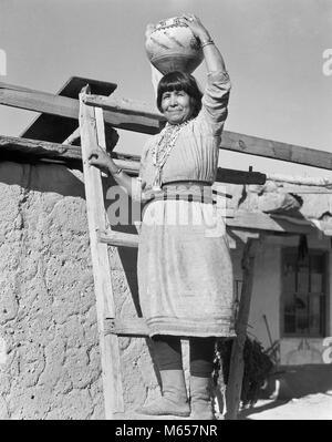 1930 Native American Indian WOMAN STANDING HOLDING OLLA POTERIE POT D'EAU SUR SA TÊTE COCHITI PUEBLO NOUVEAU MEXIQUE Banque D'Images