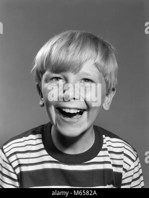Années 1950 Années 1960 SMILING RIRE HEUREUX DE ROUSSEUR FACE GARÇON BLOND PORTANT DES TEE SHIRT À RAYURES DENNIS Banque D'Images