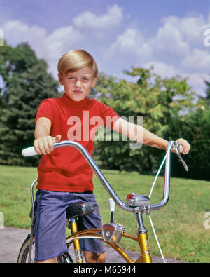 1960 garçon PORTRAIT BLONDE WEARING RED SHIRT ASSIS SUR UN VÉLO avec un guidon CRUISER PYRAMIDE LOOKING AT CAMERA Banque D'Images