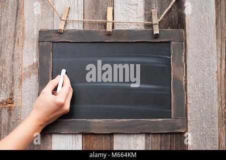 La femelle de dessiner quelque chose sur le tableau noir à la craie Banque D'Images