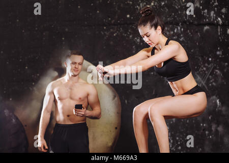 Woman jumping on fit fort avec male trainer Banque D'Images