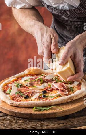 Pizza et Chef. Le chef du restaurant prépare une pizza et décore avec du parmesan. Banque D'Images