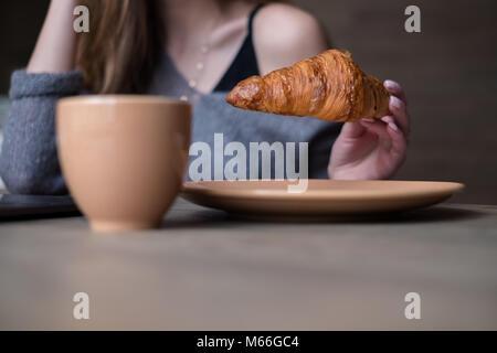 Femme mangeant un croissant Banque D'Images