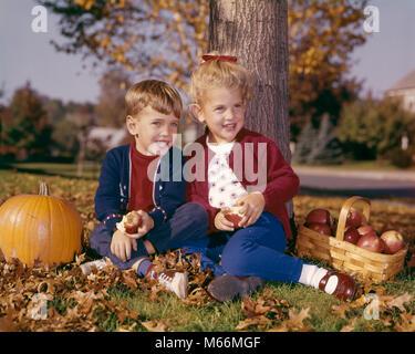 1960 SMILING BOY AND GIRL EATING APPLES ASSIS EN VERTU DE L'ARBRE D'AUTOMNE À LA CITROUILLE ET PANIER DE POMMES Banque D'Images