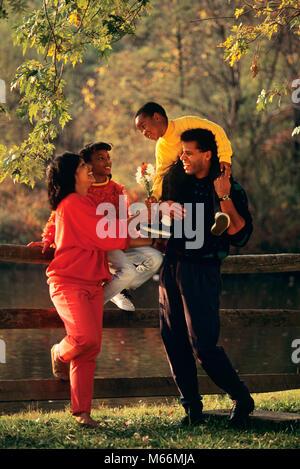 Années 1990, African American FAMILY STANDING BY FENCE EN AUTOMNE BOY HANDING FLEURS POUR MAMAN - kj12498 DEG002 Banque D'Images
